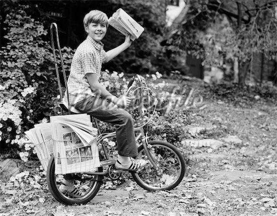 846-02792031 © ClassicStock / Masterfile Model Release: No Property Release: No 1970s SMILING DELIVERY NEWSBOY ON BICYCLE ABOUT TO TOSS NEWSPAPER LOOKING AT CAMERA